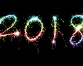 Glowing colourful numbers 2018 on black background.